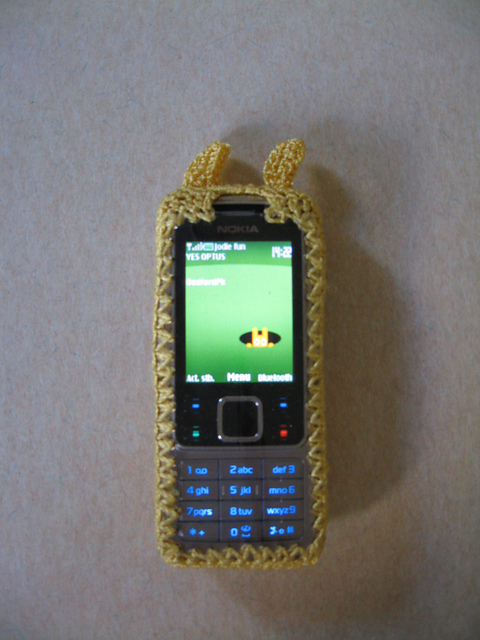 Mobile phone inside the rabbit cover. The screen side is covered in clear plastic sheet and bordered by yellow crochet. The yellow 'ears' can be seen at the top. The screen shows a green background with a yellow rabbit poking its head out of a black hole.